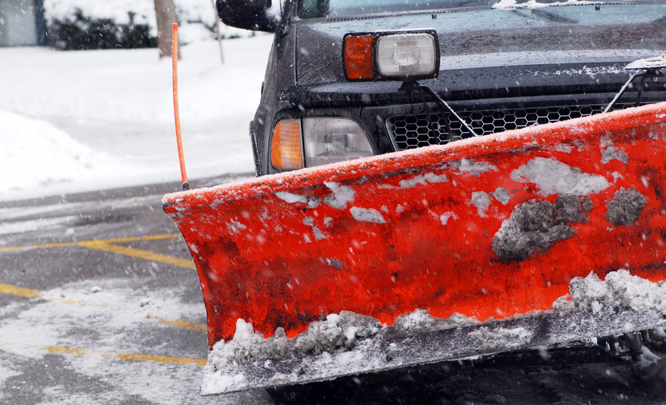 Snow plow truck on a road during a snowstorm