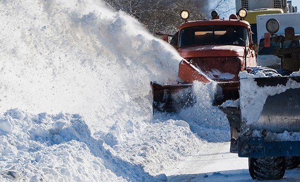 Several snow plows clearing a snowy highway.