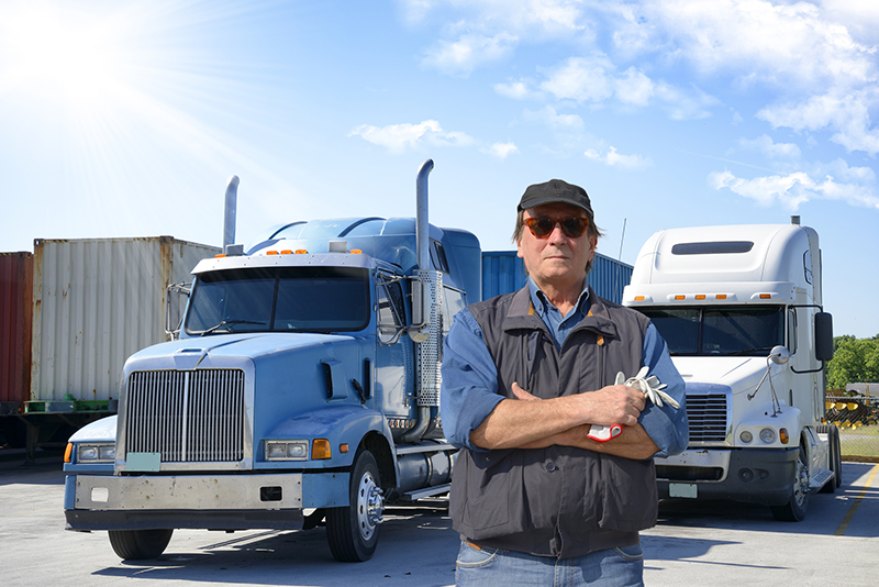 Truck driver standing in front of semi-trucks with his arms crossed.