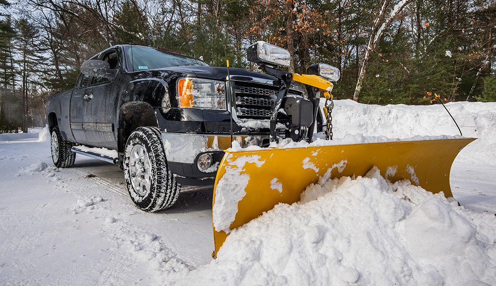 Pickup truck with a snow plow truck attachment and mounted lights.